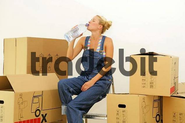 Young blonde woman surrounded by cardboard boxes, taking a break from moving