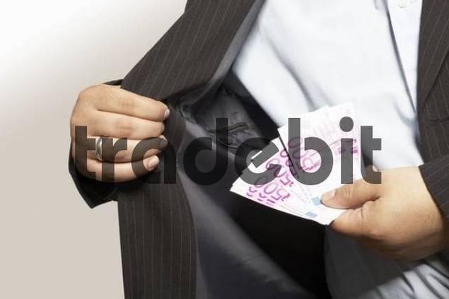 Businessman puts money in his pocket