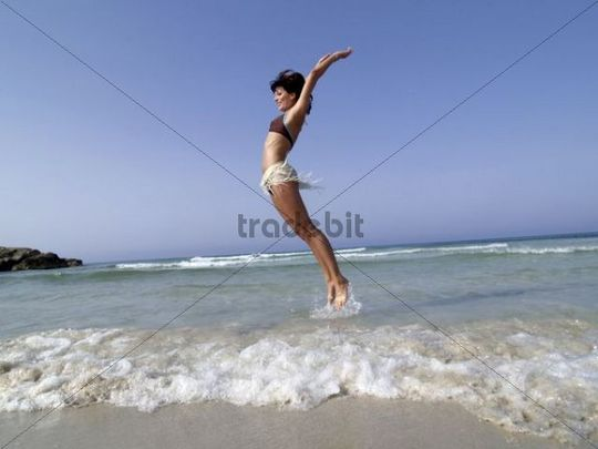 young woman jumping in the air with joy, beach of Majorca, Spain, Europe