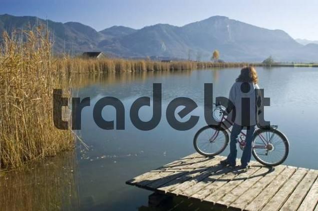 woman with bicycle at Lake Kochel, Bavaria, Germany