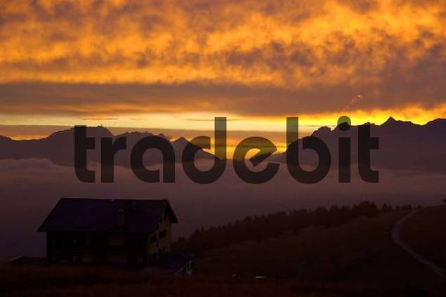 Evening sky above a mountain hut and mountain range with orange coloured clouds Haute-Savoie France