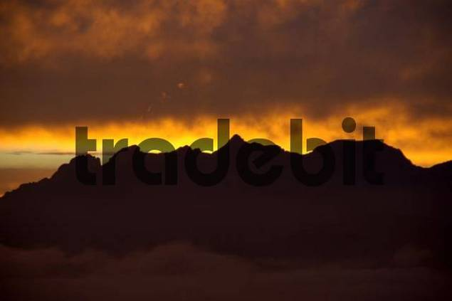 Evening sky above a mountain range with orange coloured clouds Haute-Savoie France