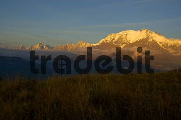 Mt. Blanc mountain glows at alpenglow with cross in meadow Haute-Savoie France