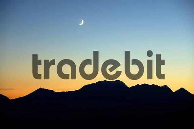 Evening sky with moon and evening star above mountain range at orange sky Haute-Savoie France