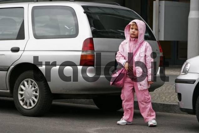little girl waits between parking cars to cross the street