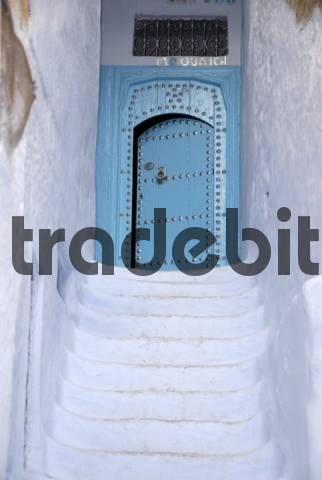 White stairs lead up to a blue gate medina Chefchaouen Morocco