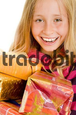Blond girl carrying a lot of presents, laughing