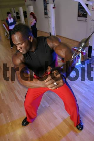 Black athlete working out with rubber bands at a gym
