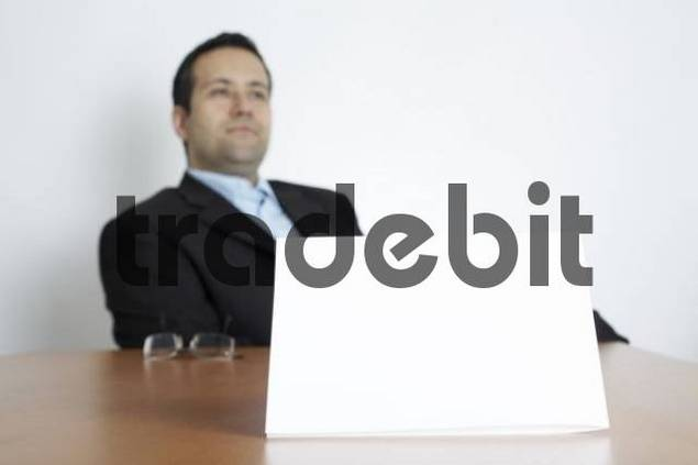 White sheet of paper, businessman sits behind his desk