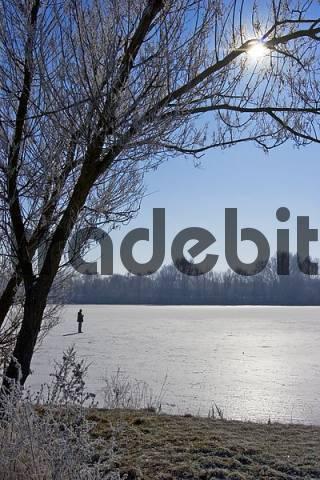 man walks over a frozen lake, against sun