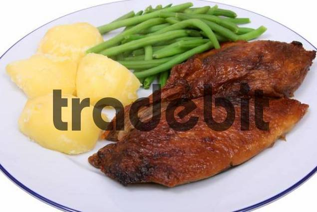 roasted duck with vegetables potatoes and beans, served on a plate