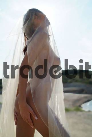 Naked young woman wrapped in transparent cloth on the beach in Mallorca, Spain, Europe