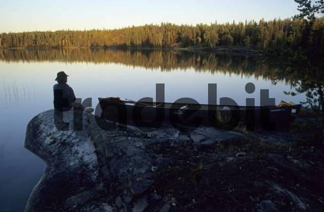 man sitting on a lakeshore in the evening light, Northwest Territories, Canada