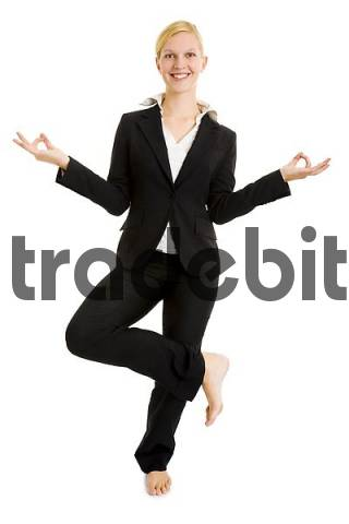Blond businesswoman balancing on one leg