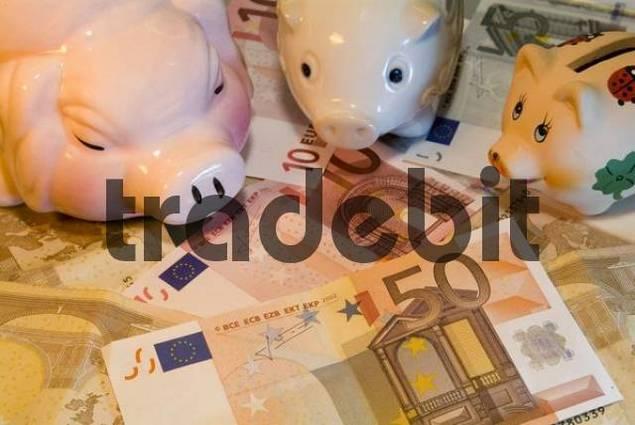 different piggybanks on Euro banknotes