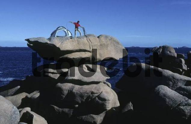 Climber erecting a tent on Roche tremblante Shaking Rock near Ploumanach, Brittany, France