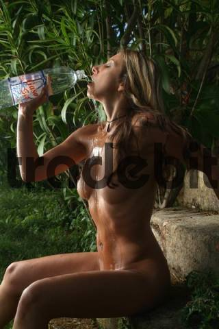 Nude, young woman drinking from and cooling off her body with a bottle of water