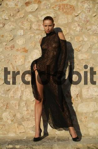 Sexy young woman wearing see-through black lace dress standing in front of the earth-coloured facade of a finca, traditional Spanish country home, Mallorca, Balearic Islands, Spain, Europe