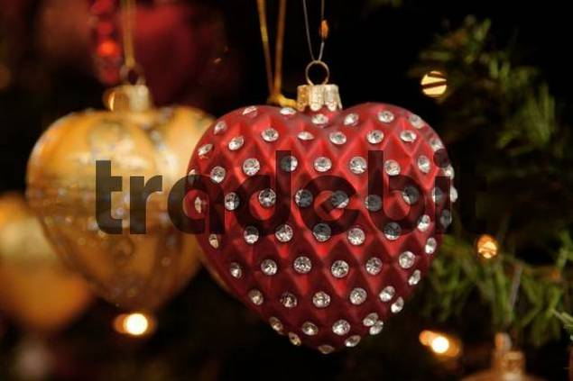 Heart-shaped Christmas ornaments crested in glass beads hung on Christmas tree
