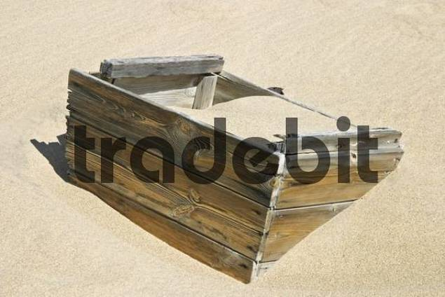 In sand sunken wooden box in the former diamondtown ghosttown Kolmanskop in the Namib desert, Luederitz, Namibia, Africa