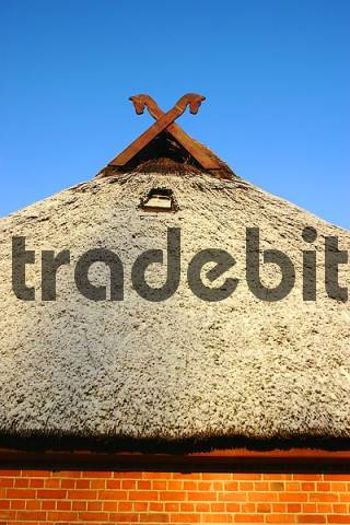 gable cross upon reed-covered ancient house