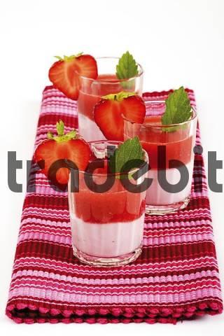 Glasses filled with strawberry yogurt, strawberry puree, garnished with strawberry slices and lemon balm