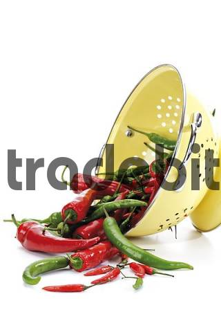 Red and green chilis in a sieve