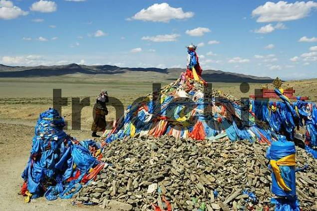 Pile of stones with prayer flags Ovoo in wide open steppe Mongolia