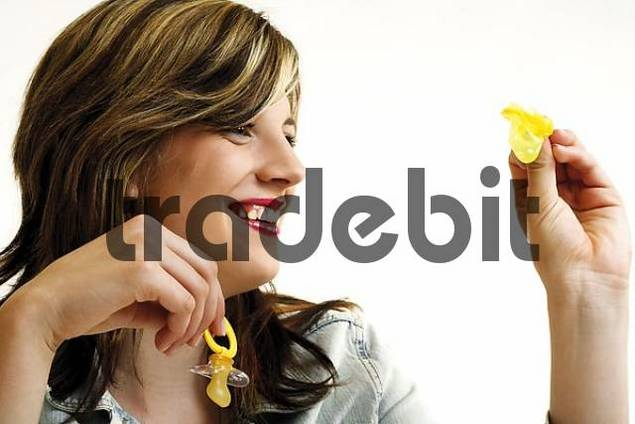 Young woman looking smilingly at a condom and holding a soother in the other hand - symbol for child or career