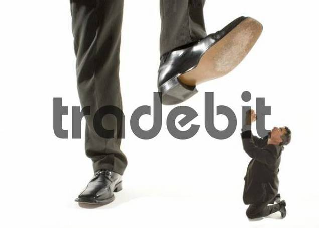 giant foot stepping on a kneeling businessman praying for mercy