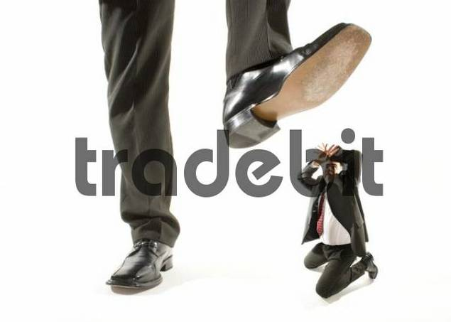 giant foot stepping on a kneeling businessman