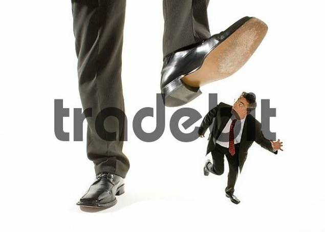giant foot stepping on a kneeling businessman running away