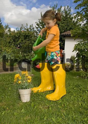 girl watering her yellow flowers wearing yellow rubber boots