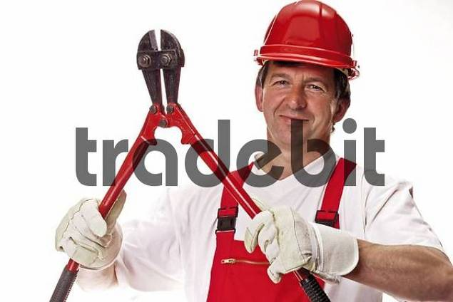 Mechanic wearing red overall and red construction helmet, holding a bolt cutter