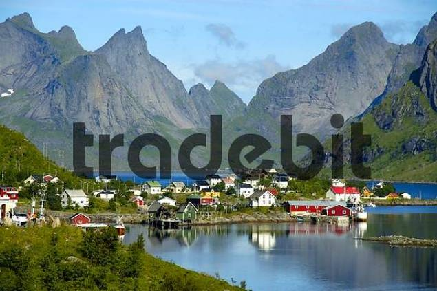 Rough mountains and houses reflect in the fjord Reine Moskenesoya Lofoten Norway
