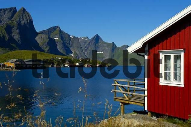 Red wooden house mountains and fjord Hamnoya Moskenesoya Lofoten Norway