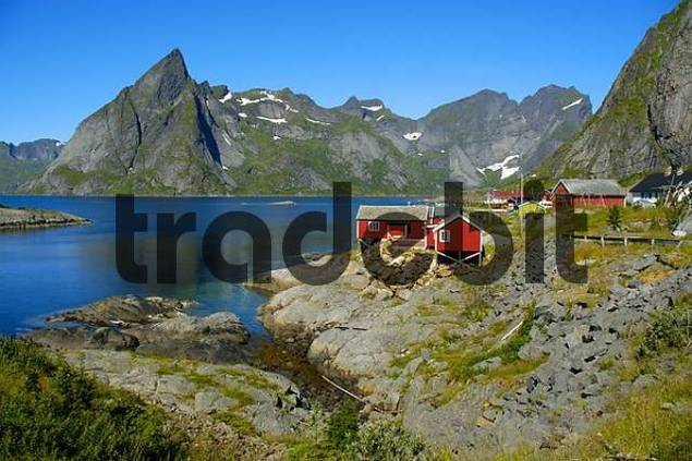 Red wooden house mountains and fjord Hamnoya Moskenesoya Lofoten Norway