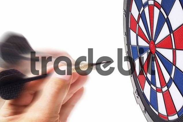 A hand holding a dart and aiming at a dartboard
