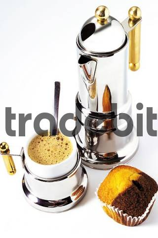 Cup of espresso, a piece of marble cake, and a silver espresso pot