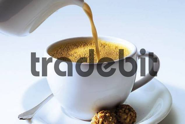 Pouring condensed milk into a cup of coffee