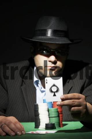 Poker player wearing sunglasses holding an ace card