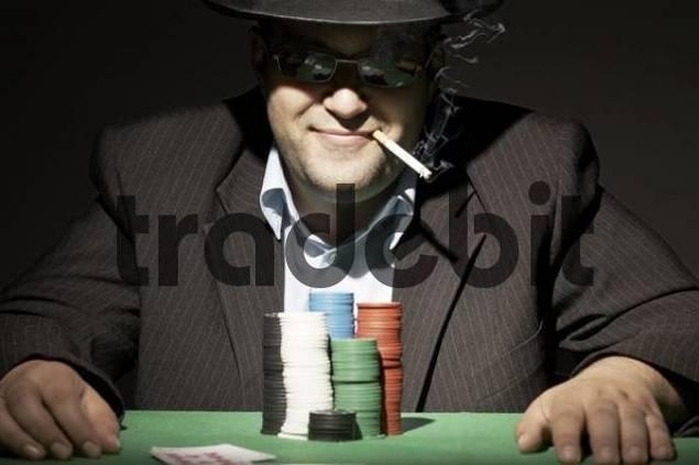 Poker player wearing sunglasses smoking a cigarette