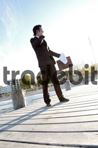 Businessman wearing a suit engaged in a stressful phone call with a client