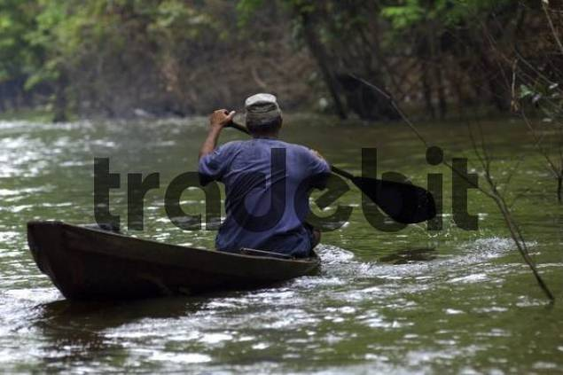 Local paddles in dugout boat on the Amazon river Brazil
