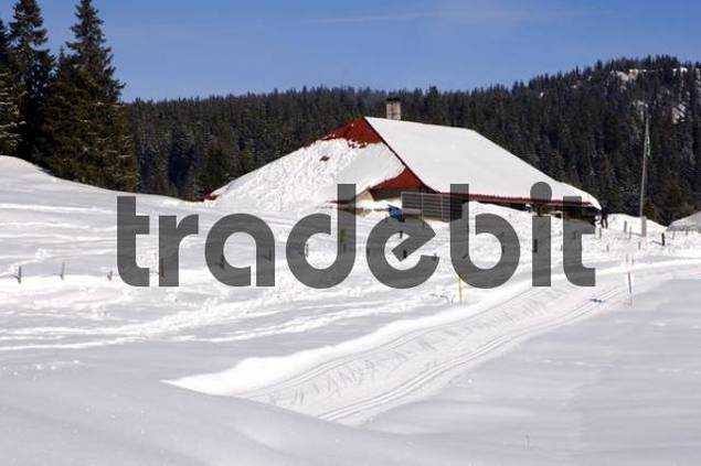 Unpopulated cross country tracks passing by a snow-covered farm house with solar energy panel Jura Switzerland