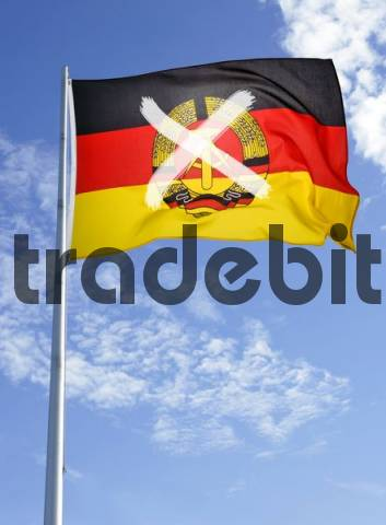 GDR flag crossed out on flagpole in front of a cloudy sky