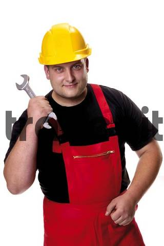 Tradesman wearing yellow hardhat holding an open-end wrench