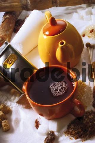 Small teapot and a cup of black tea resting on a bed of sugar with rock candy and brown sugar: tea for one