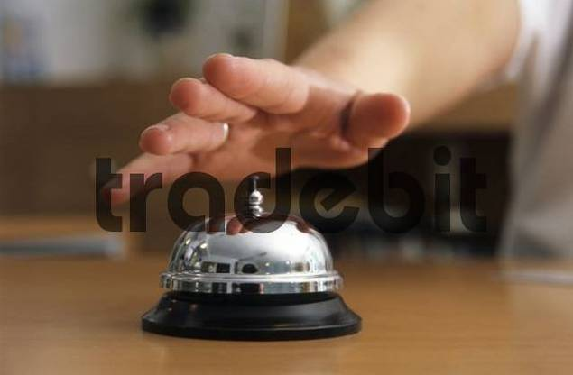 Hand about to ring a table bell at the doctors office