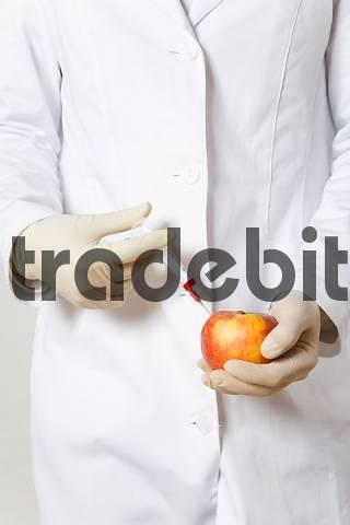 Chemist injecting an apple